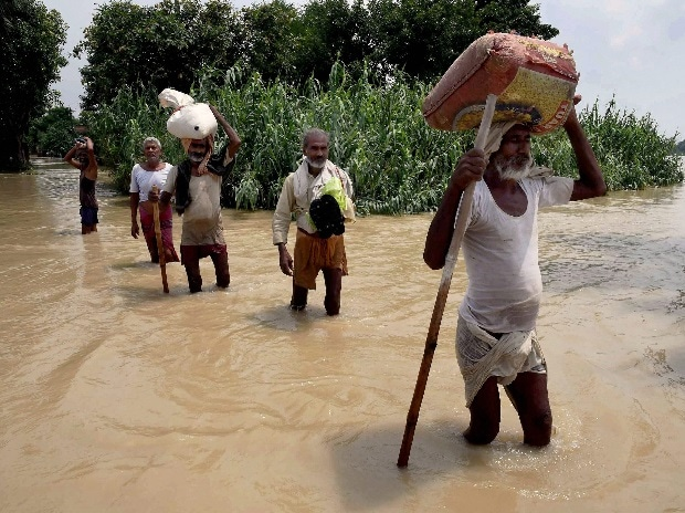 Flood-hit people shift with their belongings at Runni Saidpur in Sitamarhi district in Bihar on Thursday. File Photo: PTI
