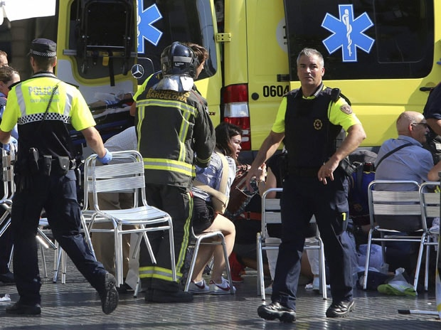 Injured people are treated in Barcelona after a white van jumped the sidewalk in the historic Las Ramblas district, crashing into a summer crowd of residents and tourists and injuring several people, police said. Photo: PTI/AP