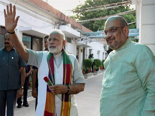 Prime Minister Narendra Modi waves at supporters as BJP President Amit Shah looks on, prior to a meeting with chief ministers of BJP ruled states. Photo: PTI