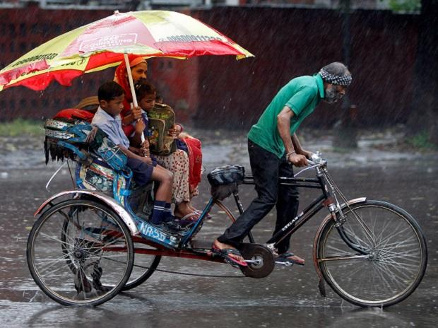 A woman and her children ride in a rickshaw during heavy rains in Chandigarh. (Photo: Reuters)