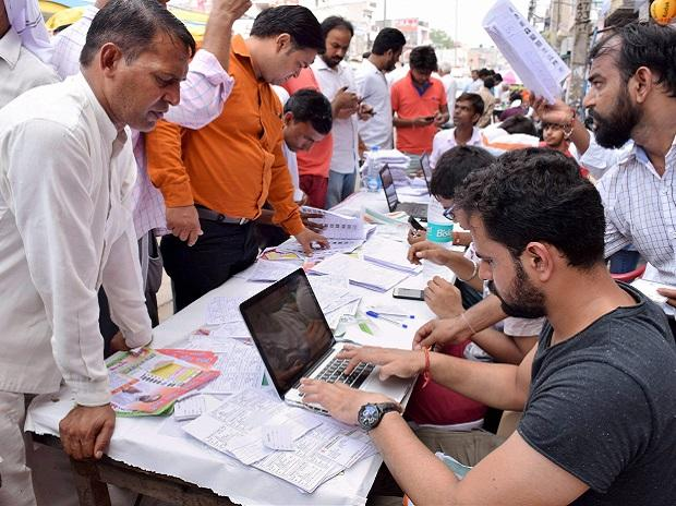 Voters complete the formalities before casting votes for Bawana assembly seat by-election, in Delhi. (Photo: PTI)