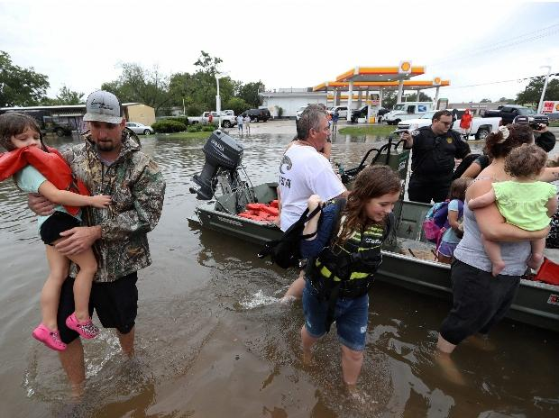 Friendswood  : Neighbors use their personal boats to rescue Friendswood, Texas residents stranded by flooding Sunday, Photo: AP/PTI
