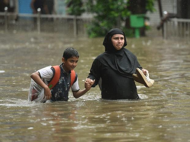 People walk along a flooded street during heavy rain showers in Mumbai. Photo: PTI