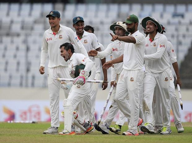 Bangladesh's cricket team captain Mushfiqur Rahim, second left, and his teammates celebrate their victory against Australia during the fourth day of their first test cricket match in Dhaka, Bangladesh
