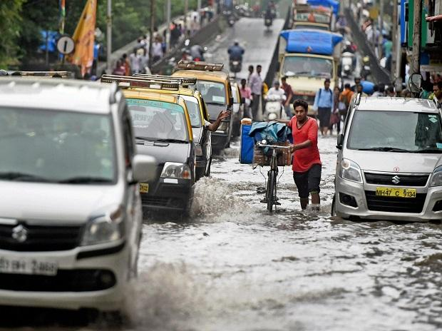 Vehicles plying at a waterlogged road after heavy rains, in Mumbai. Photo: PTI