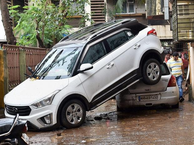 A car is seen piled over another, presumably after being drifted by flood-water during Tuesday's heavy downpour, at Shri Krishna Nagar in Borivali, Mumbai