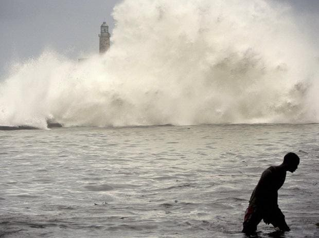 A man walks on Havana's sea wall as the ocean crashes into el Morro light house, after the passing of Hurricane Irma in Havana, Cuba. Photo: PTI