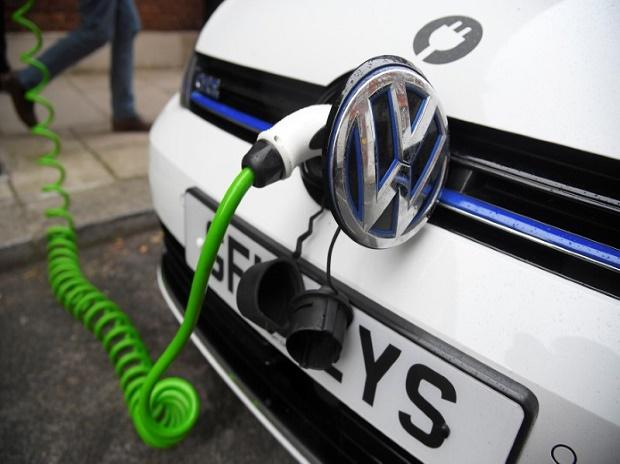 An electric Volkswagen car is plugged into a recharging point in central London