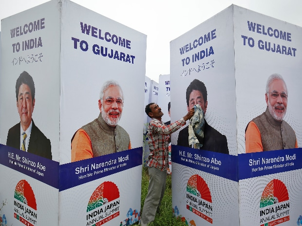 A worker cleans a hoarding featuring India's Prime Minister Narendra Modi and his Japanese counterpart Shinzo Abe ahead of Abe's visit in Ahmedabad. (Photo: Reuters)