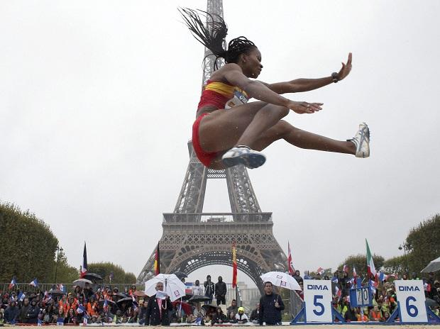 Nigerian-born Spanish athlete Juliet Itoya performs a high jump in front of the Eiffel Tower ahead of the vote in Lima, Peru, awarding the 2024 Games to the French capital, on the Champs de Mars garden in Paris