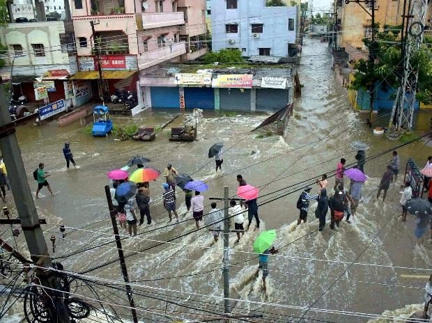 Hyderabad: People standing on flooded streets after overnight rains, in Hyderabad on Thursday. PTI Photo