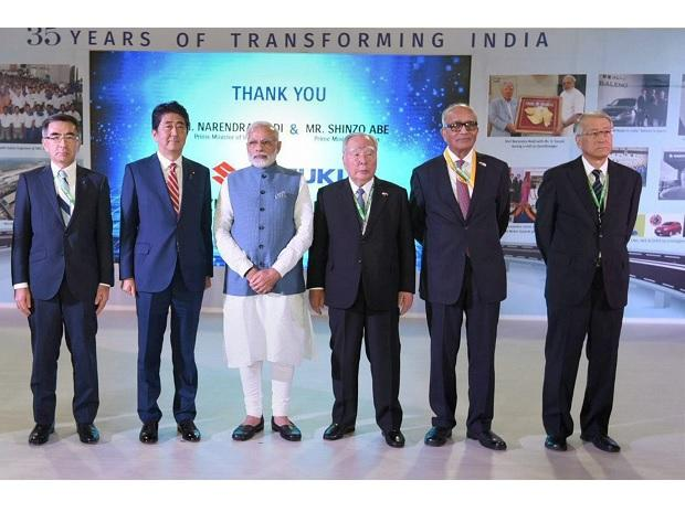 Prime Minister Narendra Modi and the Prime Minister of Japan, Shinzo Abe along with Suzuki chairman Osamu Suzuki (3rd R) and others at the Suzuki exhibition booth during India-Japan Annual Summit at Mahatma Mandir Centre in Gandhinagar. Photo: PTI