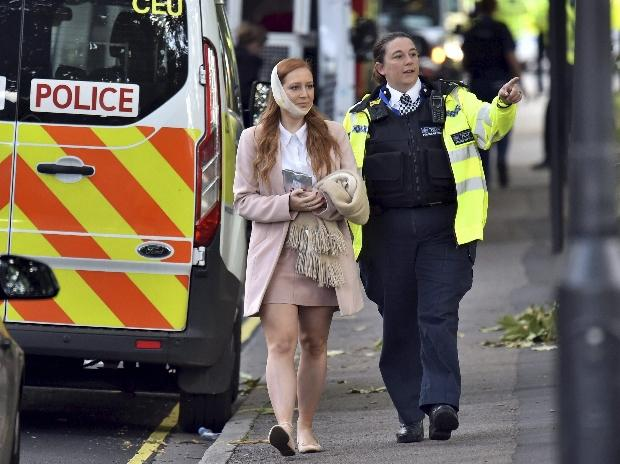 An injured woman is assisted by a police officer close to Parsons Green station in west London after an explosion on a packed London underground train. (File Photo)