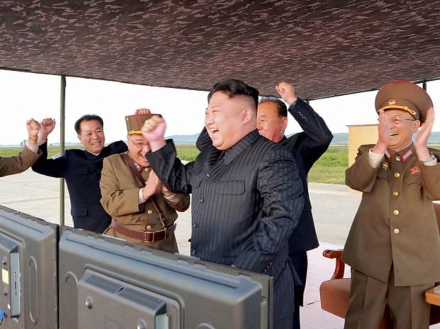 North Korean leader Kim Jong Un, center, celebrates what was said to be the test launch of an intermediate range Hwasong-12 missile at an undisclosed location in North Korea. Photo: PTI | AP