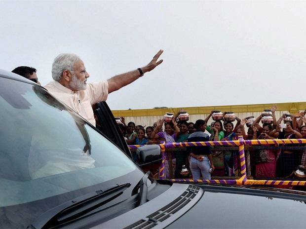 Prime Minister Narendra Modi waves to people during his arrival  in Amreli, Gujarat on Sunday. Photo: PTI