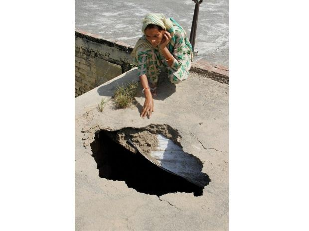 A woman shows the damaged roof of her house after firing from Pakistan side of the border, at a village in Arnia Sector about 45km from Jammu. Photo: PTI