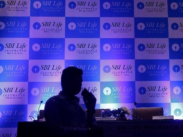 A man walks past a podium set up at the venue of a news conference to announce the launch of Initial Public Offering by SBI Life Insurance Co in Mumbai. Photo: Reuters