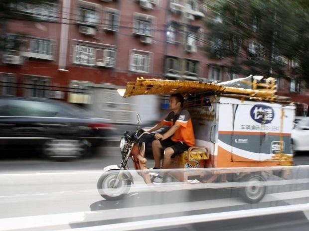 Driver Lei Wentao of the Chinese express parcel delivery firm Shentong (STO) Express rides his cargo tricycle in Beijing, China. Image: Reuters