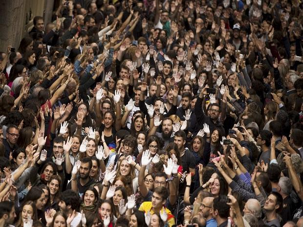 Catalan independence supporters raise their hands, some painted in white, as a symbol of protest, as they shout slogans during a rally outside the city hall of Girona, Spain. (Photo: AP | PTI)