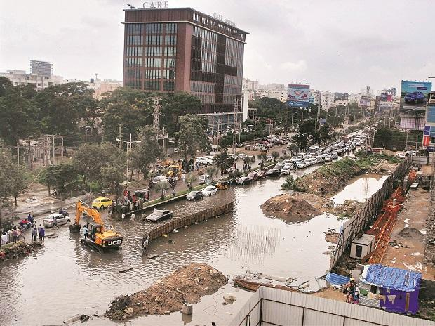 Vehicles ply on a flooded road following heavy rain in Hyderabad on Tuesday. 	Photo: PTI