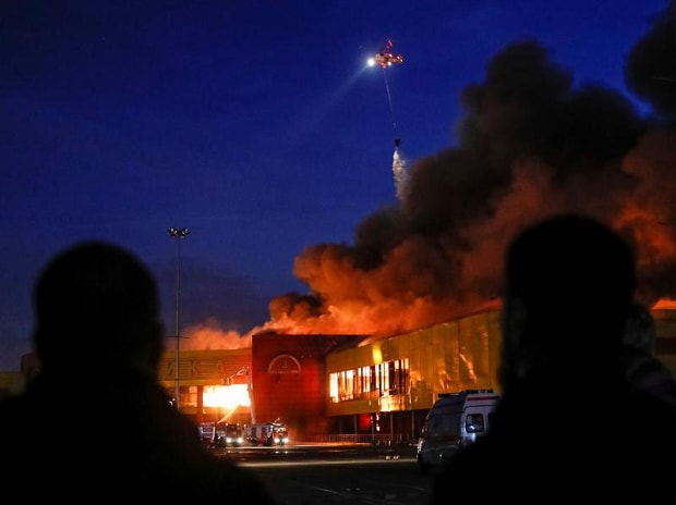 People watch as a helicopter dumps water on a fire at a construction goods market on the northwestern edge of Moscow, Russia