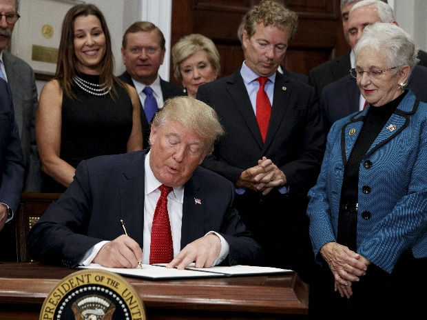 President Donald Trump signs an executive order on health care in the Roosevelt Room of the White House in Washington. (Photo: AP| PTI)