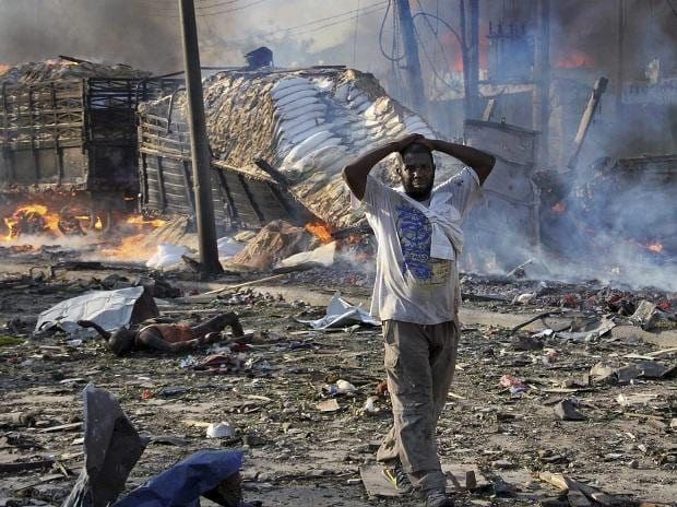 A Somali gestures as he walks past a dead body, left, and destroyed buildings at the scene of a blast in the capital Mogadishu, Somalia. Photo: PTI