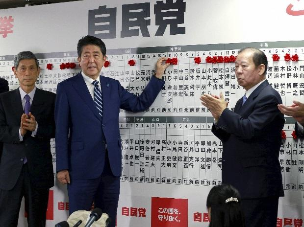 Japanese Prime Minister Shinzo Abe, leader of the Liberal Democratic Party, poses for photos as he marks on the name of one of those elected in the parliamentary lower house election at the party headquarters in Tokyo. Photo: PTI