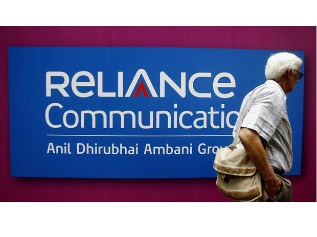 A man walks past a logo of Reliance Communication before the Annual General Meeting in Mumbai. (Photo: Reuters)