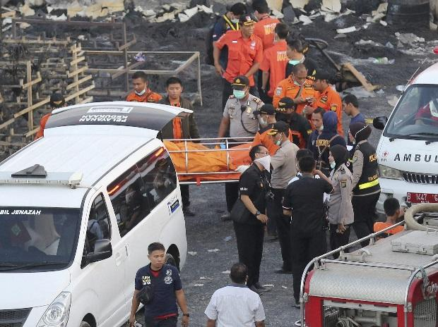 Police officers and rescuers carry a body at the site of an explosion at a firecracker factory in Tangerang, on the outskirts of Jakarta, Indonesia. Photo: AP/PTI