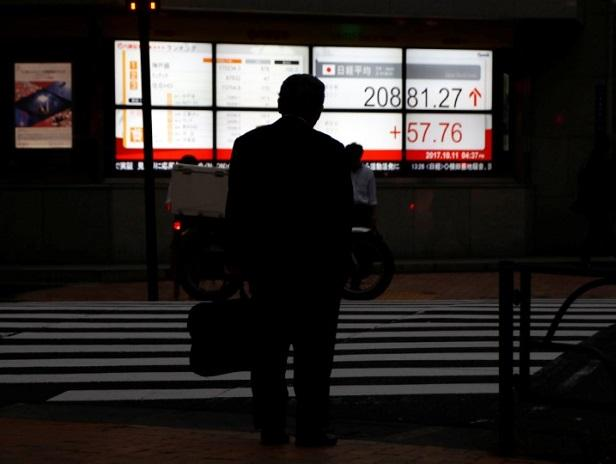 A man stands in front of an electronic board showing Japan's Nikkei average outside a brokerage in Tokyo. (Photo: Reuters)
