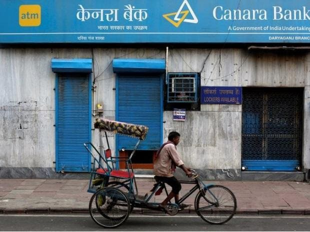 A rickshaw puller passes the Canara Bank branch in the old quarters of Delhi. Photo: Reuters