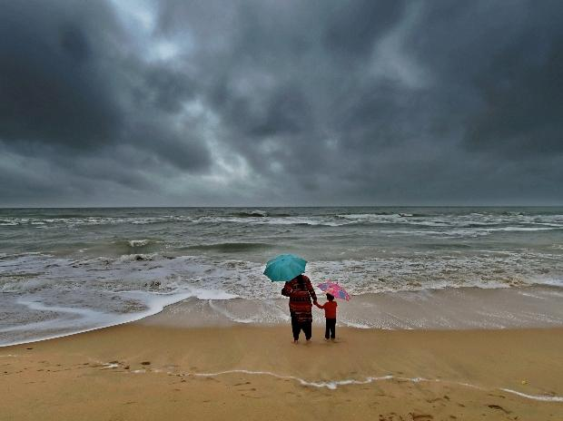 File Photo: A woman standing with her son at Marina beach following heavy downpour due to the onset of northeast monsoon in Chennai.