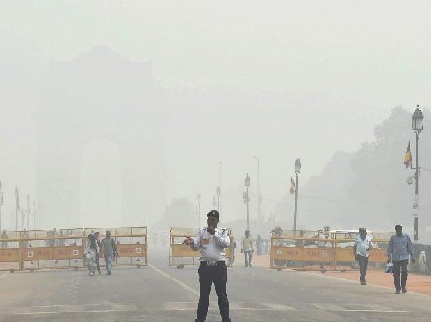 A traffic policeman discharges his duty as India Gate is enveloped in dense smog, in New Delhi. (Photo: PTI)