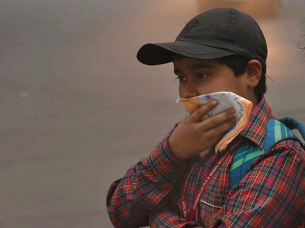 A student using his handkerchief  to cover his face as smog covers the capital's skyline on Wednesday