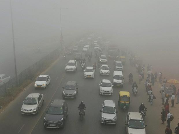 Vehicles plying at a road in smog, in New Delhi on Wednesday morning. Photo: PTI