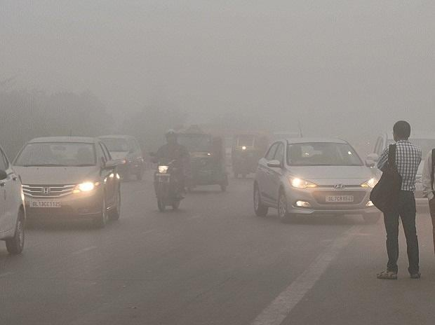 Vehicles drive through heavy smog near Akshardham Metro Station in New Delhi on Wednesday. Photo: PTI