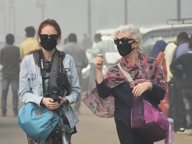 Foreign tourists wear masks to protect themselves from heavy smog and air pollution in New Delhi. (Photo: PTI)