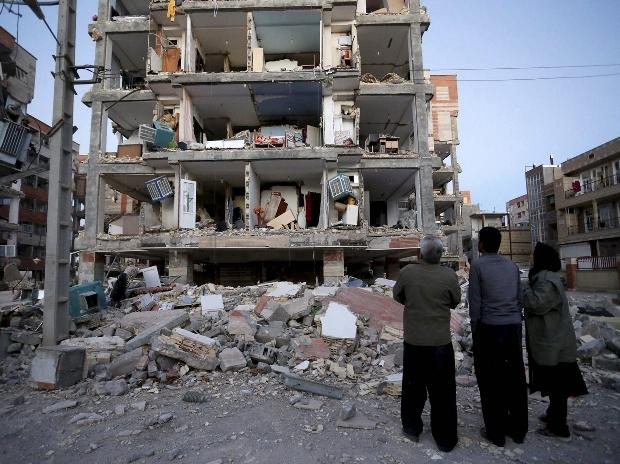 People look at destroyed buildings after an earthquake at the city of Sarpol-e-Zahab in western Iran