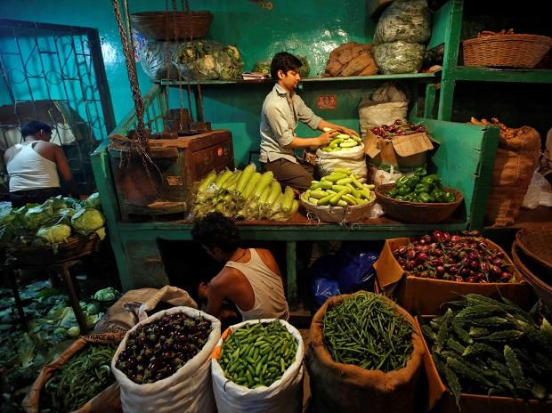 A vendor arranges vegetable at his stall in a market in Mumbai