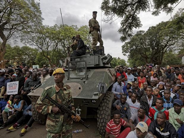 Army soldiers stand guard as protesters demanding President Robert Mugabe stands down gather on the road leading to State House in Harare. Photo: AP | PTI