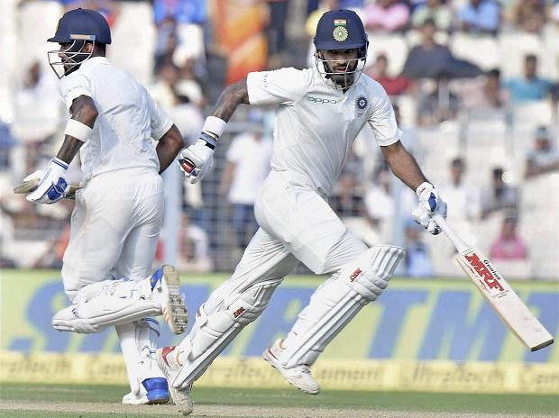 India's Shikhar Dhawan and KL Rahul cross for a run during Day 4 of the first cricket test math against Sri Lanka at Eden Gardens in Kolkata on Sunday