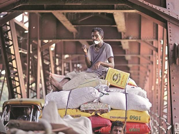A worker sitting on a cart carrying rice sacks in New Delhi. File photo: Reuters