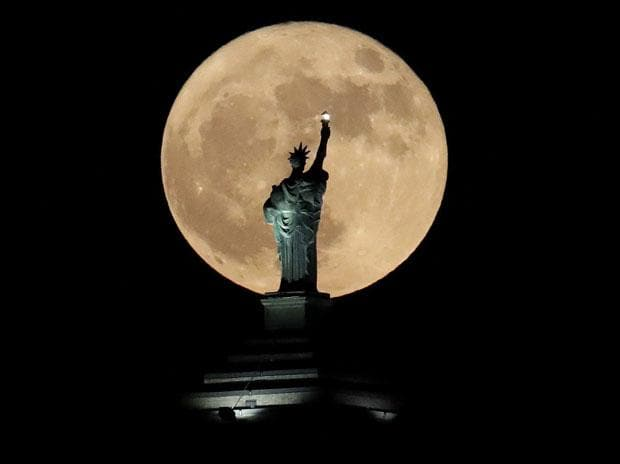 A supermoon rises in front of a replica of the Statue of Liberty sitting atop the Liberty Building in downtown Buffalo, N.Y. Photo: Reuters