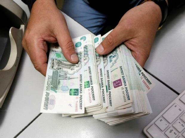 An employee counts Russian ruble banknotes at an office in Krasnoyarsk, Russia. Photo: Reuters