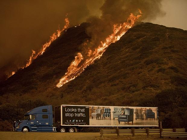 Flames from the Thomas fire burn above a truck on Highway 101 north of Ventura, California. Photo: PTI/AP