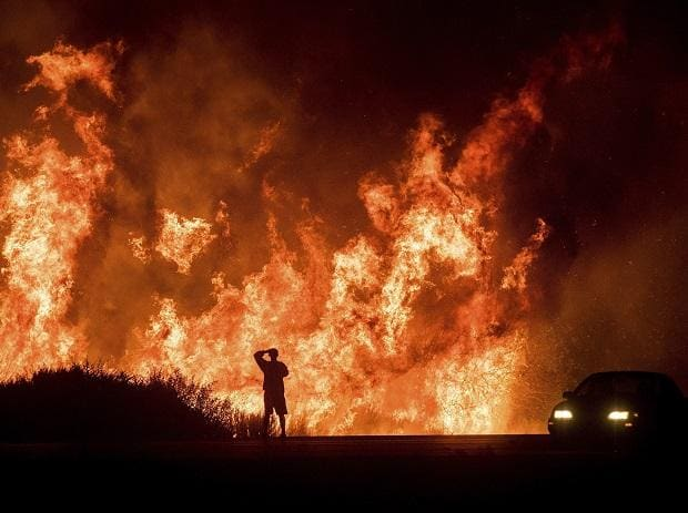 A motorists on Highway 101 watches flames from the Thomas fire leap above the roadway north of Ventura, California. Photo: PTI
