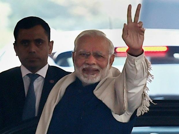 Prime Minister Narendra Modi flashes victory sign after BJP's success in Himachal and Gujarat assembly elections, on his arrival for the winter session of Parliament , in New Delhi