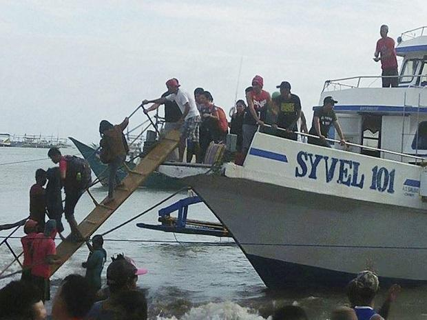Rescued passengers from the ill-fated M/V Mercraft 3 disembark from a boat which helped in the rescue operation at Infanta township, Quezon province in northeastern Philippines. Photo: AP | PTI