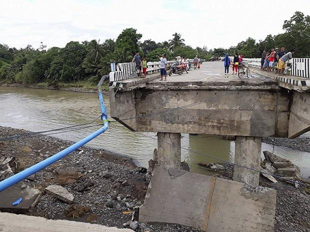 People gather on a bridge which was damaged by the onslaught of the flooding brought about by tropical storm Tembin, Sunday, Dec. 24, 2017 in Zamboanga Del Sur in southern Philippines.